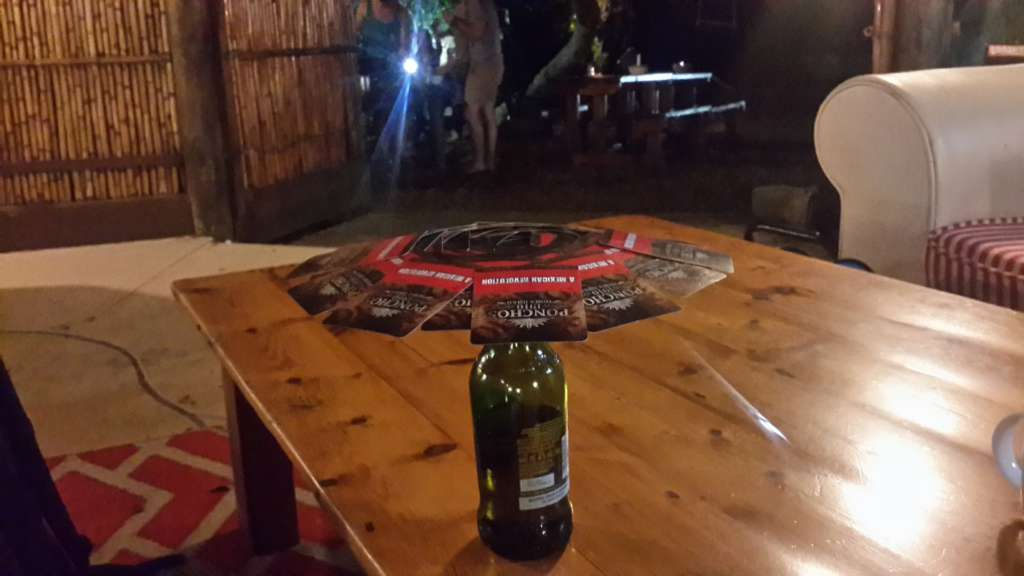 Umbrella drinking game. The first card is balanced on top of an empty bottle after which each player sets a card so that two corners can't touch existing cards. Players can settle a punishment for a player who screws up. In the picture whole deck of cards makes the umbrella. Don't be confused from the beer as I have drank only 12 portions of alcohol during four months.